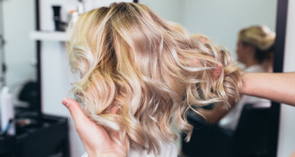 Woman with short, blonde and curled hair extensions
